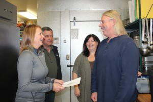 Arika Atkins and Tim Temples present a check for $5400 to volunteer Russ Neely for Meals on Wheels, as senior services manager Tammy Davies looks on.