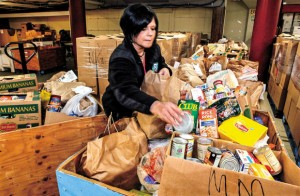Lisa Chavez is surrounded by some of the 15, 878 pounds of food collected by R.A.Long and Mark Morris high school students in their Civil War food drive for Help Warehouse.